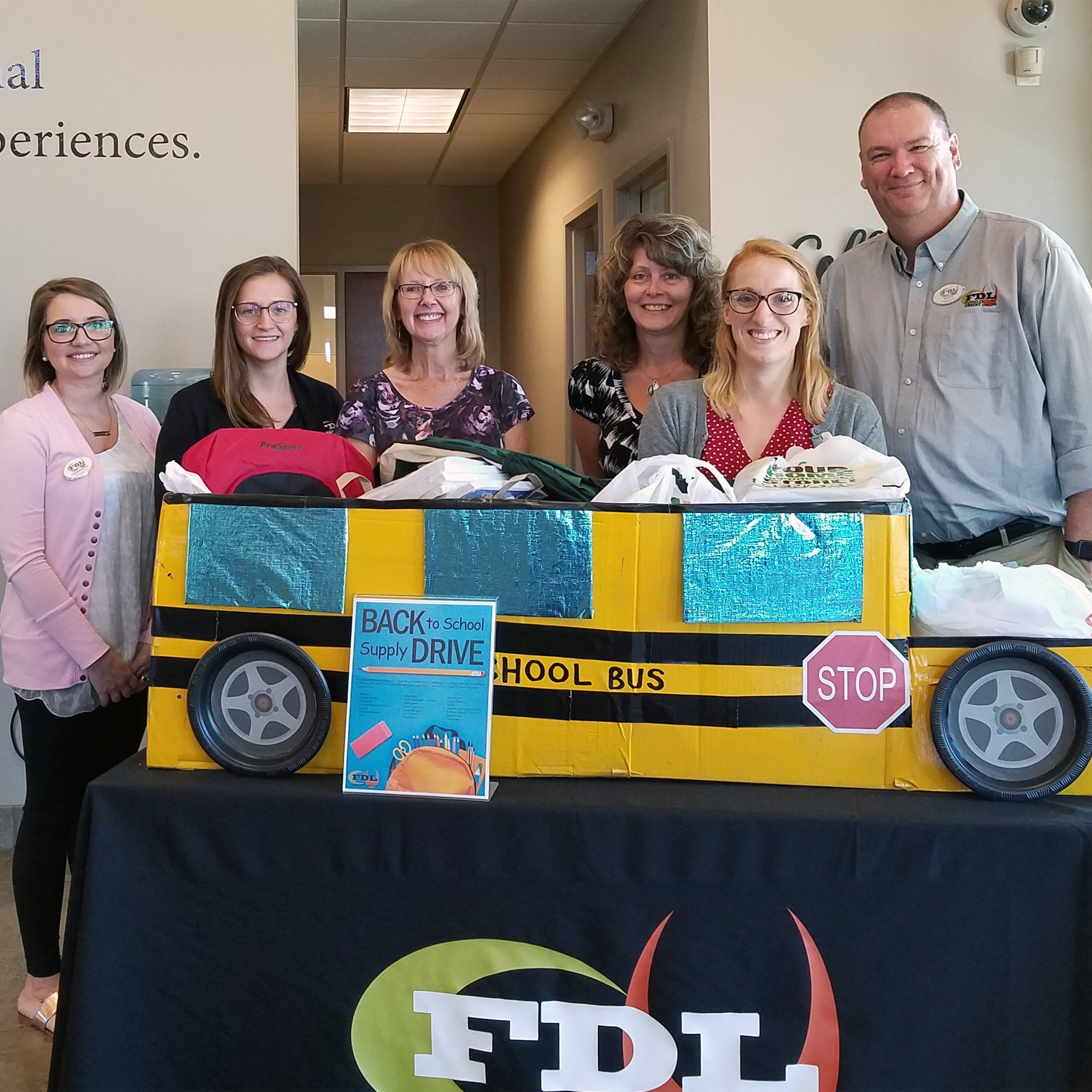 staff standing by school bus decorated box of school supplies