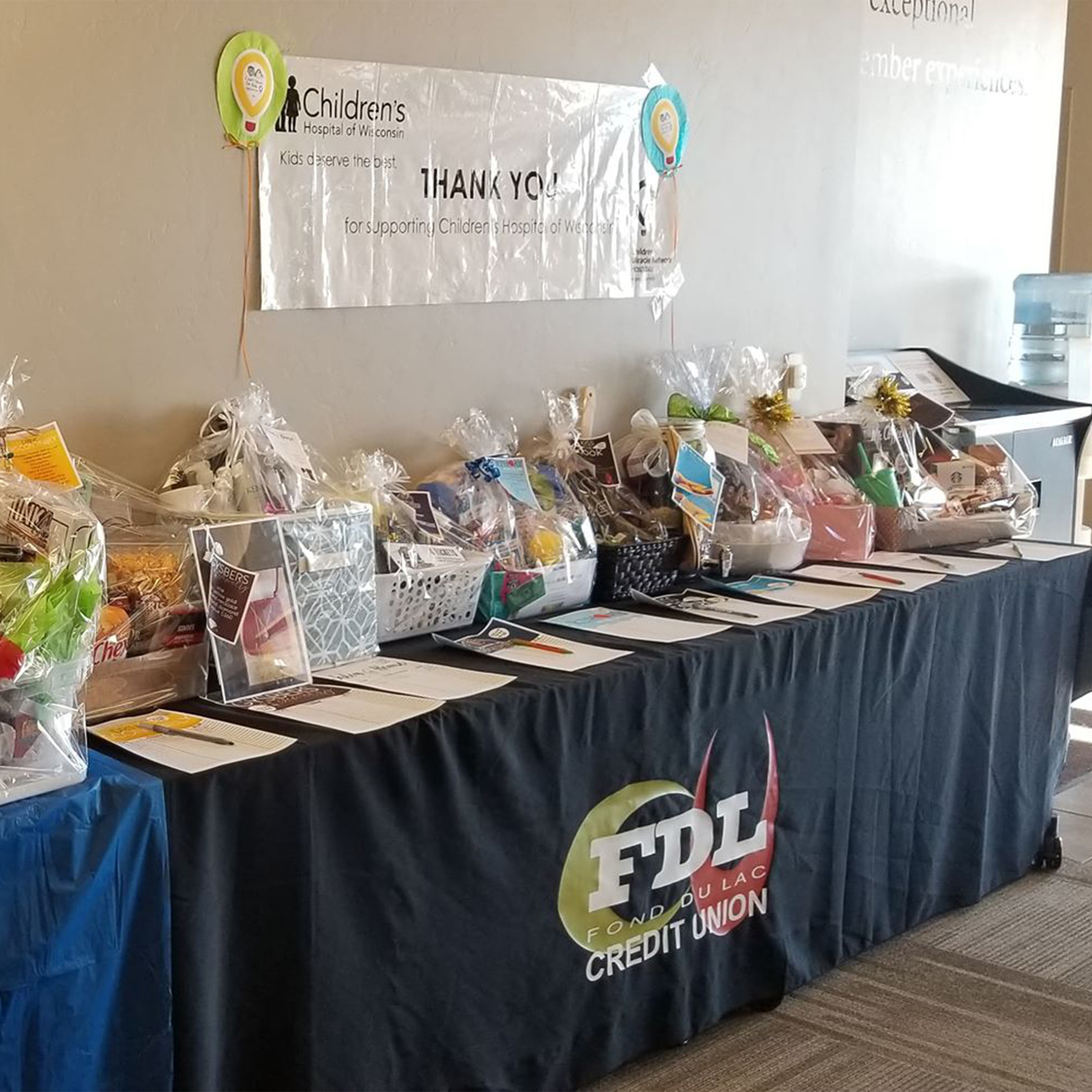 fundraising table filled with silent auction baskets