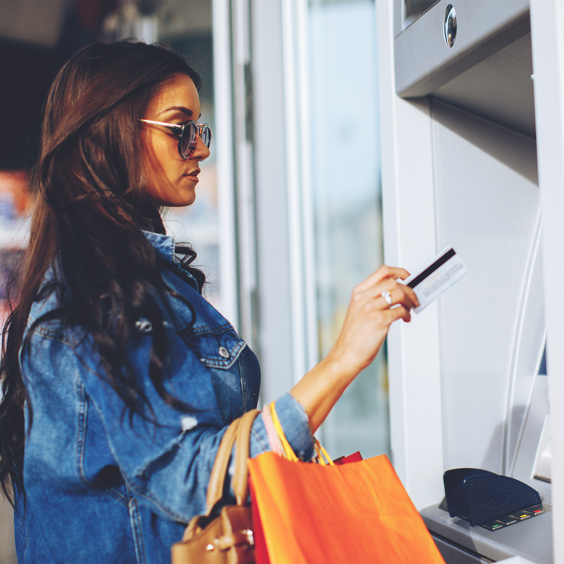 woman at atm holding debit card
