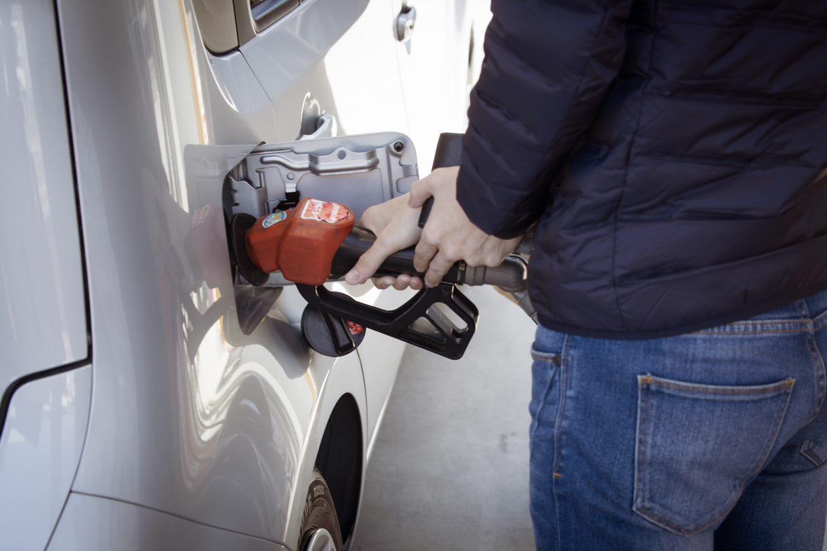 man putting gas in car