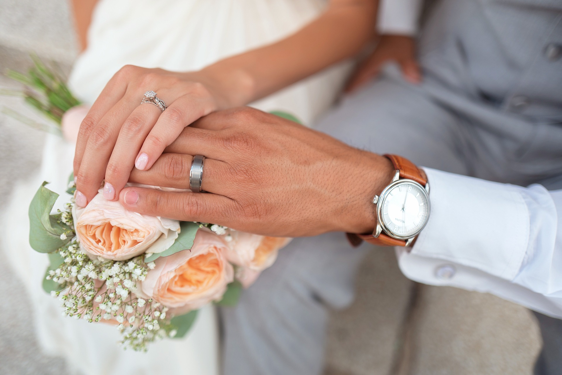 couple's hands with wedding bands on wedding bouquet